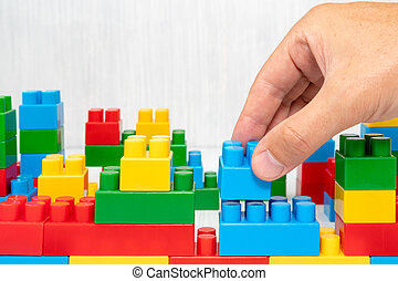 bloque plástico, en, mano, edificio, pared