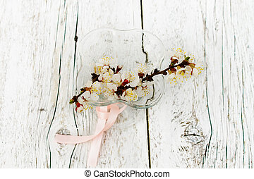 blossoming apricot branches in a glass on a white wooden backgro