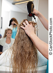 Blow Drying Wet Hair - Beautician blow drying woman's hair...