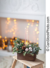 blow out the candles and smoke. Workshop of Christmas decor with their own hands. Christmas wooden box with fir branches for the holiday. The new year celebration.