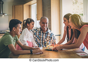 Blow out the candles! - Happy family celebrating the fathers...