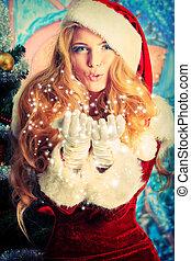 blow snowflakes - Beautiful young woman in Santa Claus...