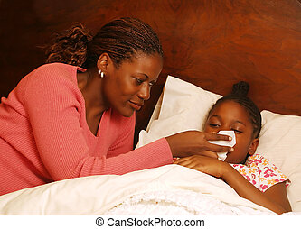 Blow - A mother helps her sick daughter blow her nose.