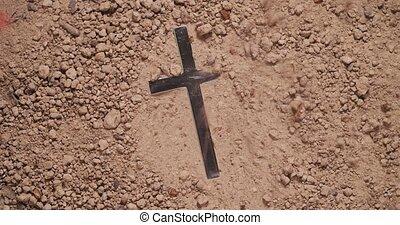 Blowing away dirt to discover hidden metal cross