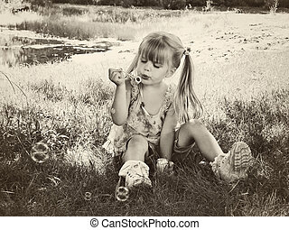 Blowing Bubbles - Little girl in sepia tones blowing...