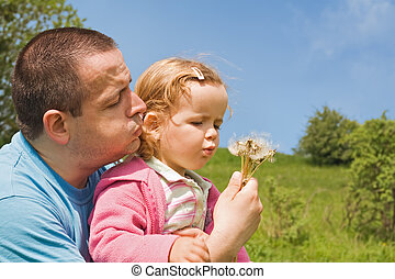 Blowing dandelion seeds - Father and little girl blowing ...