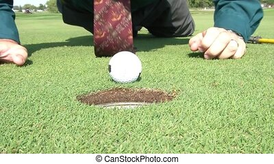 Blowing Golf Ball into Hole Businessman