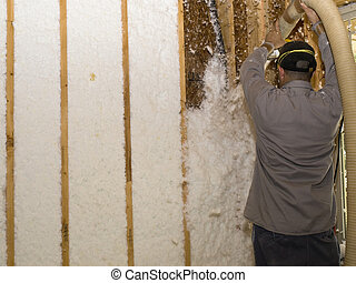 Worker blowing fiberglass insulation over his head with long hose