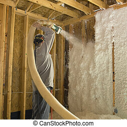 Worker blowing fiberglass insulation into the wall of a new house