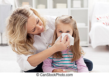 Blowing nose - Woman at home blowing the nose of her little...