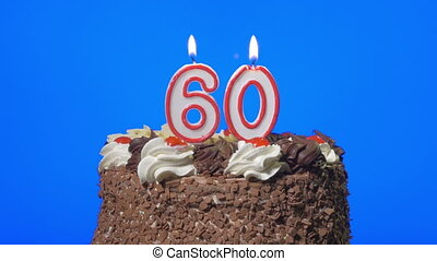 Blowing number 60 candles on a cake