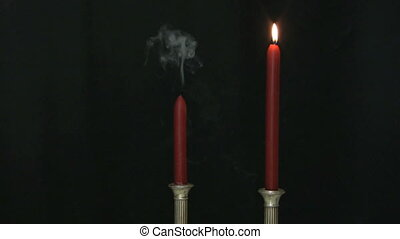 Blowing out a candle - One candle of a pair being blown out