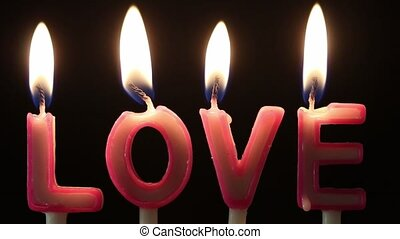 Blowing out a LOVE candles on black background. Valentine...
