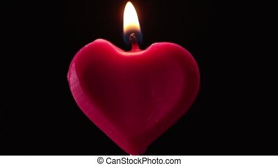 Blowing out a red heart candle on black background. love...