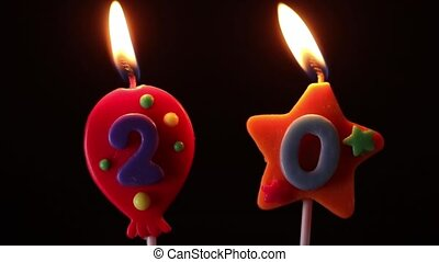 blowing out number of 20 candles on black background -...