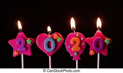 Blowing out number of 2020 candles on black background