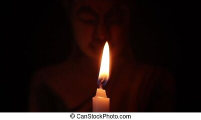 Blowing out white candle in a dark and buddha face statue on...