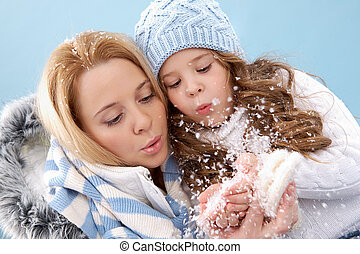 Blowing snow - Portrait of mother and her daughter blowing...