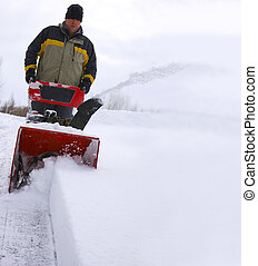 Blowing Snow - Snow blower in action clearing a driveway in...