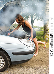 Blown engine - Young woman bending over the blown engine of...