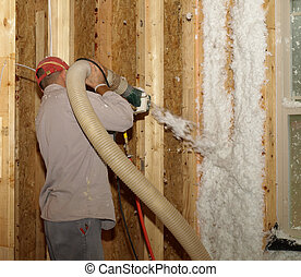 Worker blowing in fiberglass insulation in a house under construction.