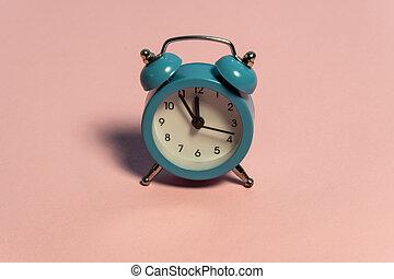 Blue alarm retro clock on pink background. Five minutes to twelve