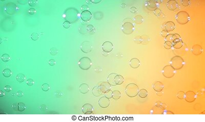 Blue and clear soap bubbles on turquoise and light orange, background, slow motion