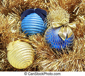 blue and golden christmas balls on a golden tinsel