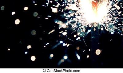 Blue and orange burning sparkler against dark background....
