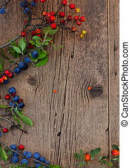 blue and red berries with green leaves on a wooden background