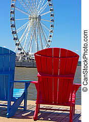 Blue and red chairs on a pier with Ferris wheel on background. Pier facing Ferris wheel with colorful wooden chairs.