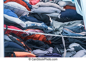 Blue and red hues of clothing in a woman's closet, folded but messy, in need of closet organization.