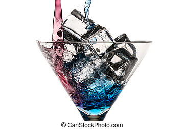 Blue and red liqueur poured into a glass with ice cubes on white background