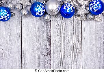 Blue and silver Christmas ornament top border on white wood...