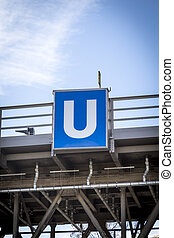 blue and white Berlin subway sign on a bridge