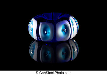 Blue and white glass bead on black background