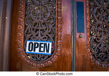 open sign on a wooden door
