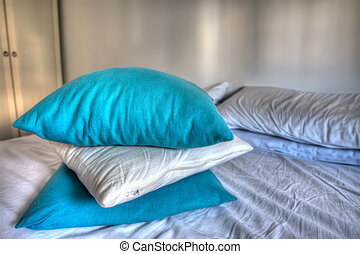 blue and white pillows on bed