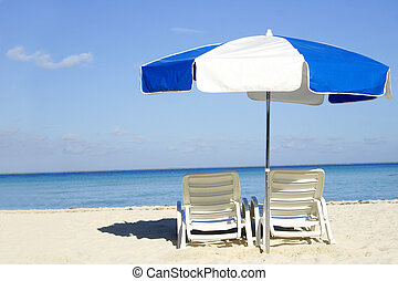Blue and White Umbrella - Umbrella and loungers on the beach