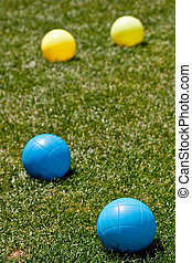 Blue and Yellow Bocce Balls in Green Grass