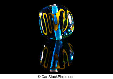 Blue and yellow glass bead on black background