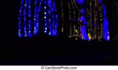 blue and yellow glowing garlands outside focus on the street, winter night