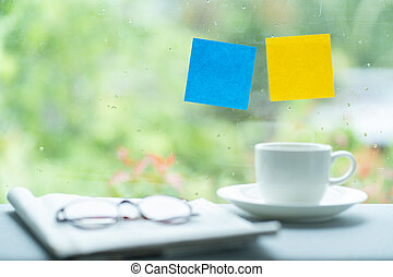 Blue and yellow post it stick on windows with blurred image of coffee cup and glasses
