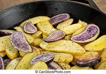 Blue and yellow potatoes in a skillet