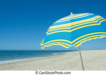 Blue and yellow umbrella on a sandy beach