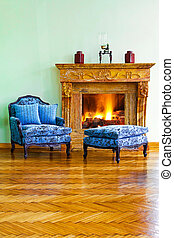 Blue armchair with leg rest and marble fireplace
