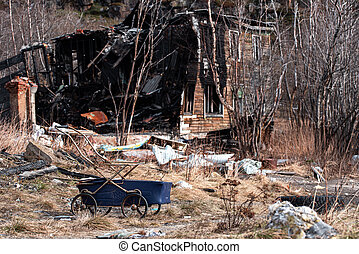 Blue baby carriage near old wooden burned-down house