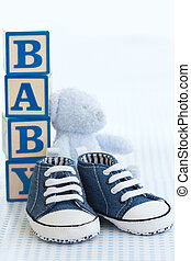 Blue denim baby shoes, baby blocks and teddy bear