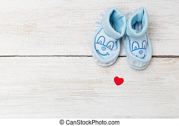 Blue baby's bootees on wooden background. Mockup