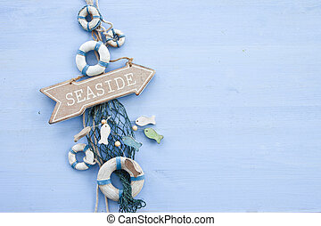 Decorative signpost to the seaside on blue wooden background